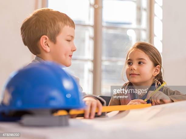Little boy and girl talking while working on blueprints.