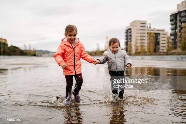 little boy and girl walking holding hands over a rain puddle - silver boot stock pictures, royalty-free photos & images