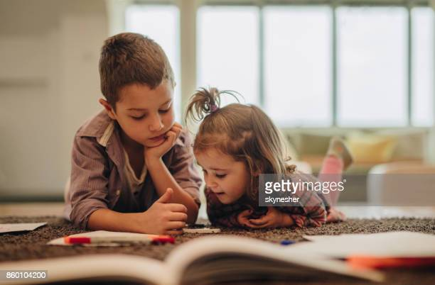 little boy and girl watching cartoons on mobile phone while relaxing on the carpet. - brother stock pictures, royalty-free photos & images