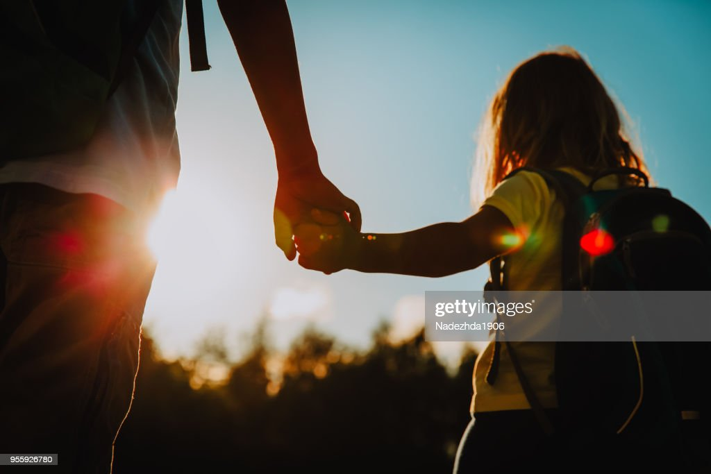 little boy and girl with backpacks holding hands at sunset : Stock Photo