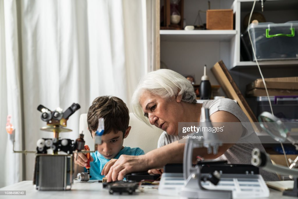 Little Boy And Grandmother Building Robot : Stock Photo