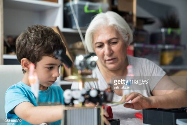 Little Boy And Grandmother Building Robot
