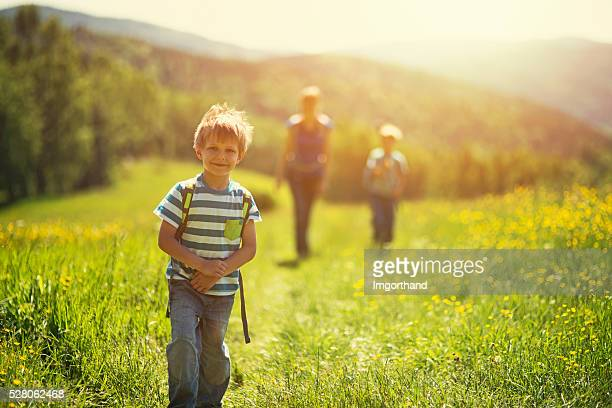 Little boy and his family hiking in sunny flowery meadow