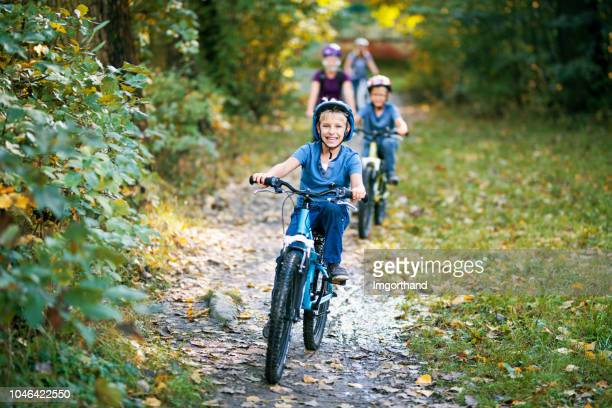 little boy and his family riding bicycles in nature - cycling stock pictures, royalty-free photos & images