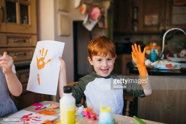 Little Boy and His Hand Print Painting