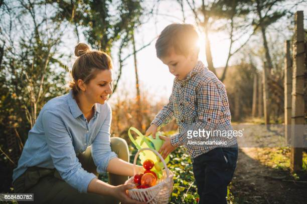 little boy and his mom on easter egg hunt - happy easter mom stock pictures, royalty-free photos & images