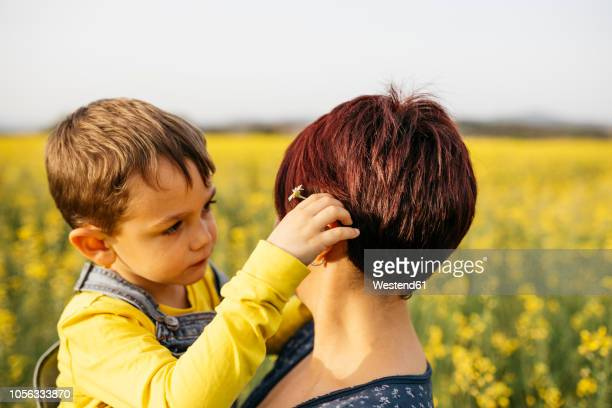 Little boy and his mother in a rape field