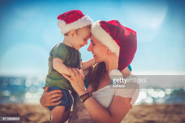 little boy and his mother on christmas on the beach - beach christmas stock pictures, royalty-free photos & images