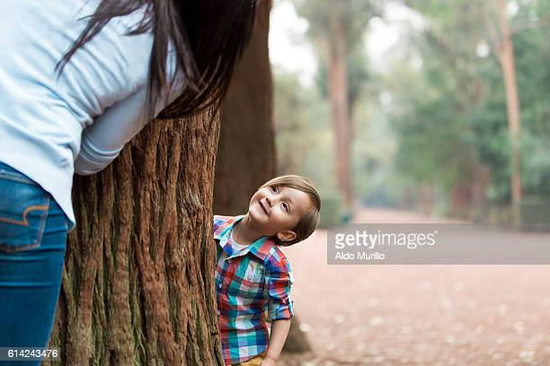 Little boy and his mother playing hide and seek