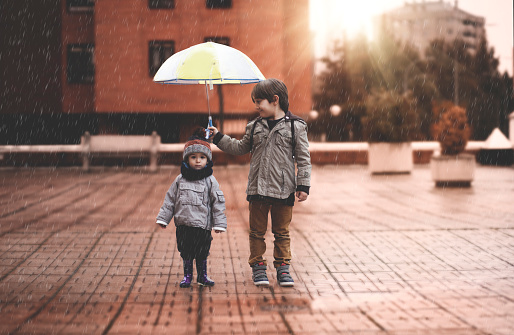 A little boy and his older brother protect themselves from the rain with an umbrella, in the city - gettyimageskorea