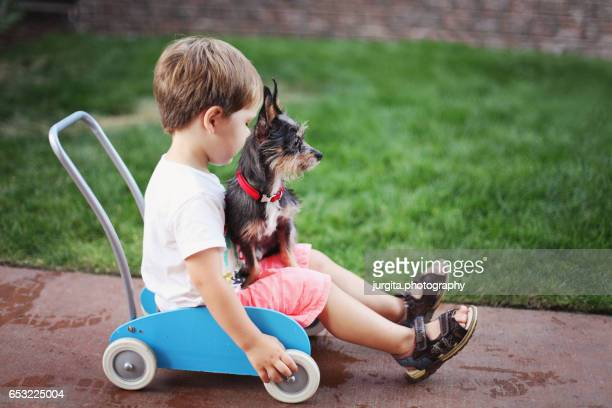Little boy and his puppy playing in the yard