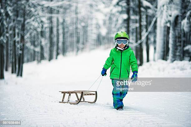 Little boy and his sled in winter worest.