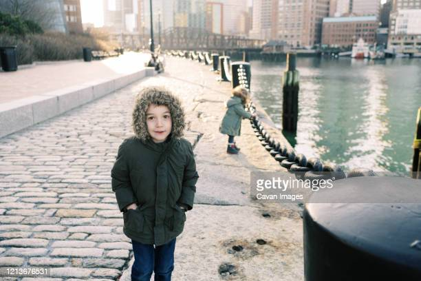a little boy and his toddler sister walking along boston harbor. - toddler at airport stock pictures, royalty-free photos & images