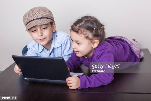 Little Boy And Little Girl Using Laptop At Home