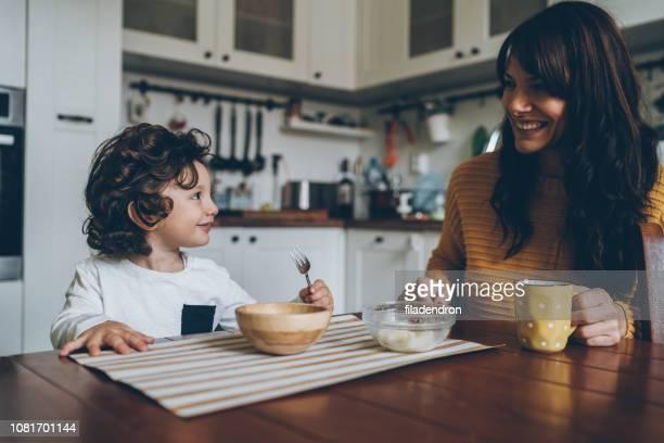 pequeño niño y mamá en la mesa - desayuno fotografías e imágenes de stock
