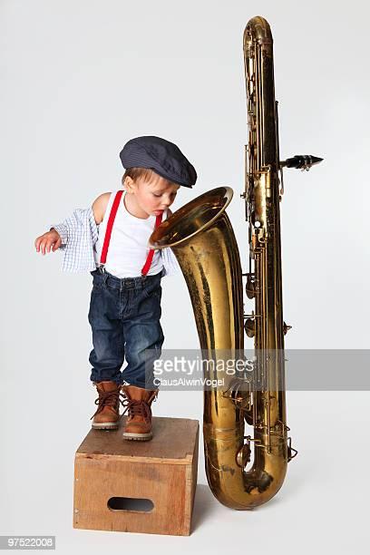 kleiner junge mit saxophon - musikinstrument stock-fotos und bilder