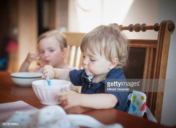 Little boy (12-23 months) and sister (2-3) eating at table