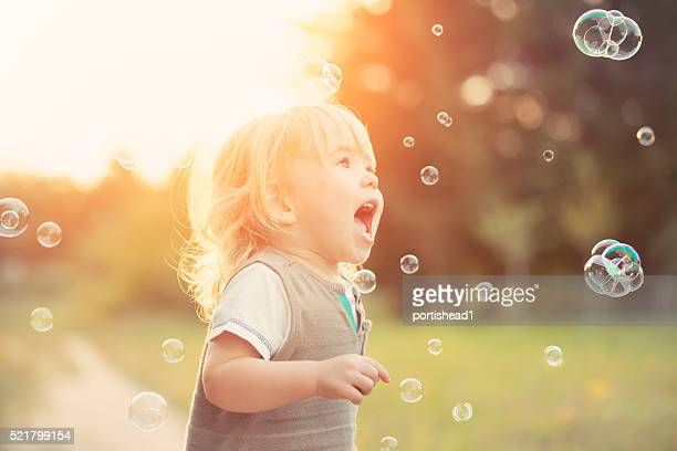 little boy and soap bubbles - peuter stockfoto's en -beelden
