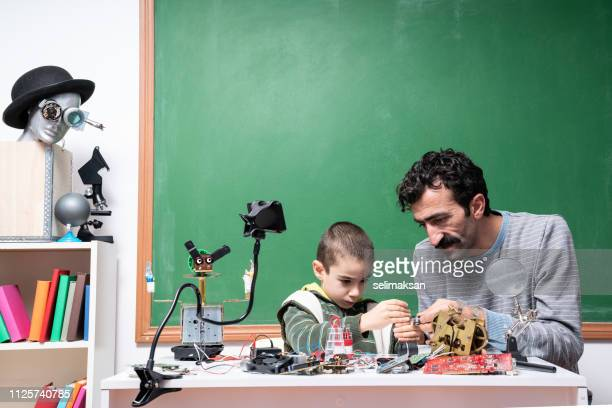 Little Boy And Teacher Working on Robotics