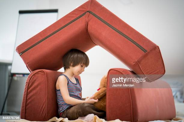 little boy and teddy bear with small house made of furniture - sicherheit stock-fotos und bilder