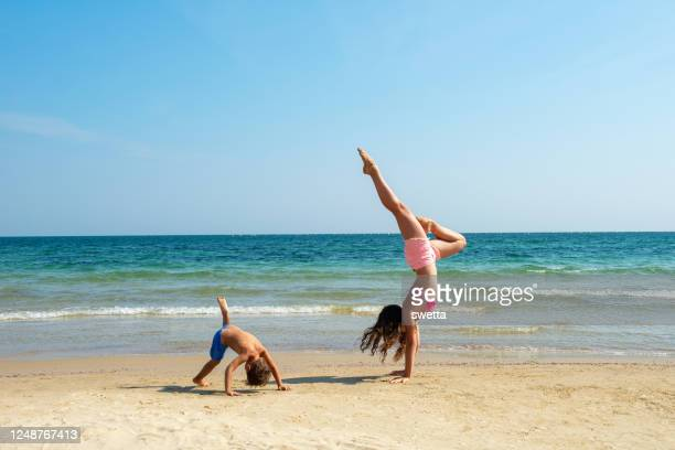 little boy and teen girl practicing handstand on beach stock photo - bulgaria stock pictures, royalty-free photos & images