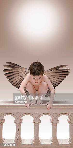 Little Boy Angel sitting on balustrade