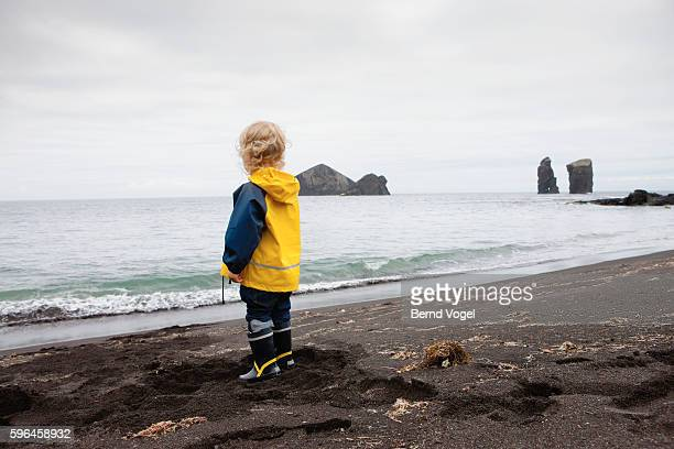 Little boy (3-4) at beach on cloudy day