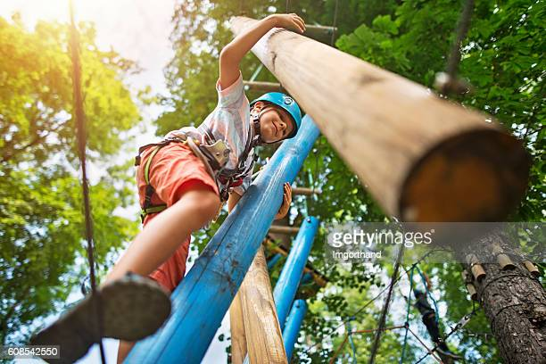 Little boy at outdoors ropes course obstacle