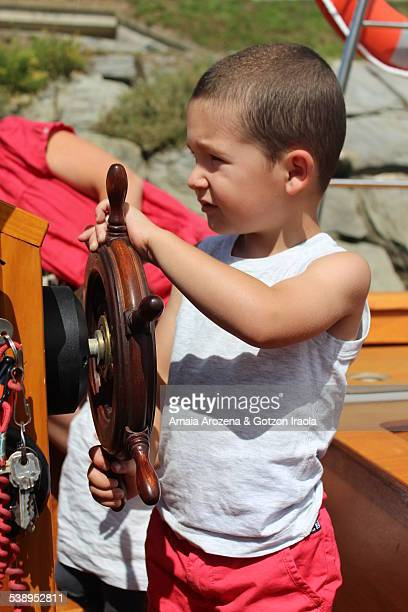 Little boy at the helm of a boat