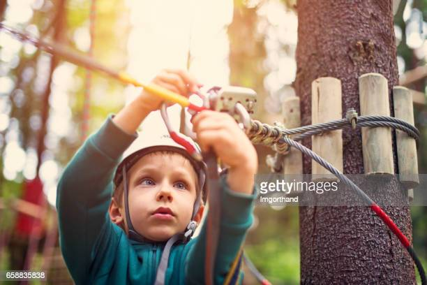 Little boy attaching carabiner to zip line