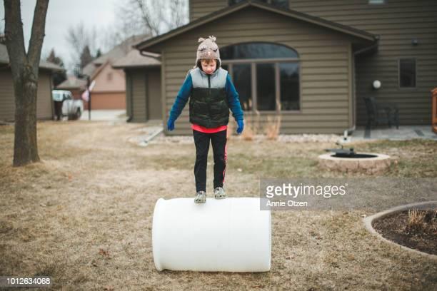 Little Boy Balancing on a Large Barrel
