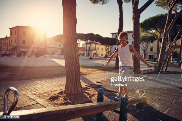 little boy balancing on seesaw in the playground. - imgorthand stock photos and pictures
