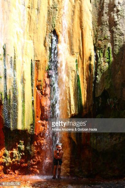 Little boy bathing in a colorful waterfall in Caldera de Taburiente National Park on the island of La Palma, Canary islands. Spain.