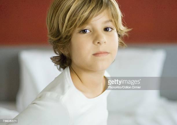 Little boy, bed in background