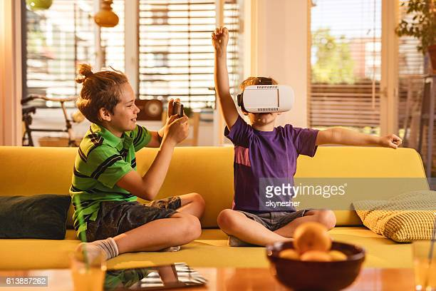 Little boy being photographed while playing with virtual reality simulator.