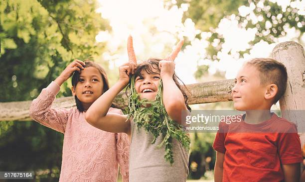 Little boy being silly with two carrots and his friends