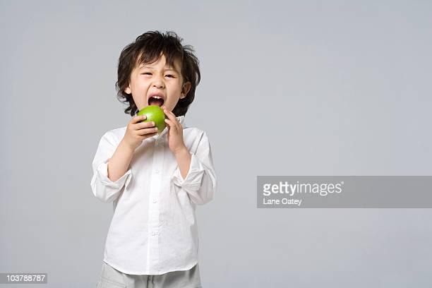 Little boy biting into an apple