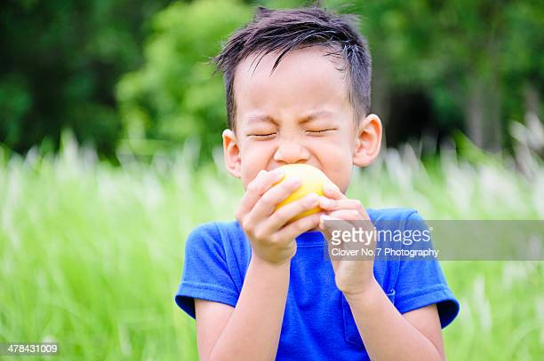Little boy biting yellow lemon.