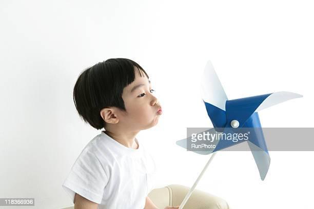 little boy blowing a paper windmill