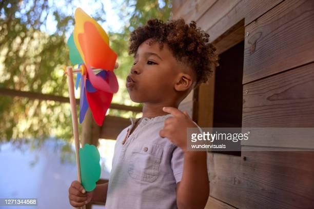 weinig jongen die kleurrijk pinwheel bovenop boomhuis blaast - onschuld stockfoto's en -beelden
