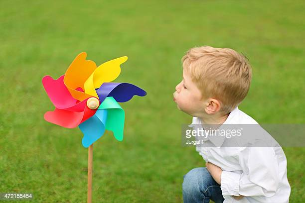 Little Boy Blowing Colorful Pinwheel Toy Against Green Grass Background