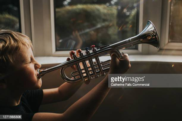 little boy blowing hard into a toy trumpet - wind instrument stock pictures, royalty-free photos & images