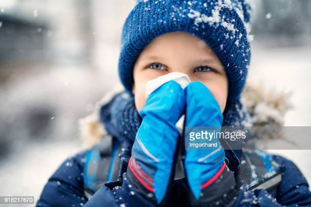 Little boy blowing nose on winter day