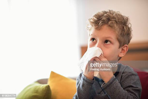 Little boy blowing nose