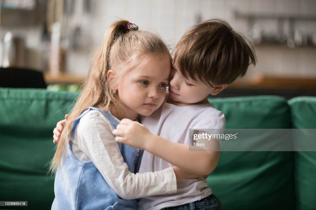 Little boy brother consoling and supporting upset girl embracing sister : Stock Photo