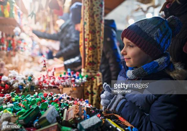 Little boy browsing toys and christmas decorations on street christmas market