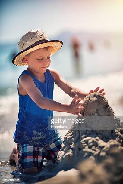 Kleine Junge Sandburgen am Strand
