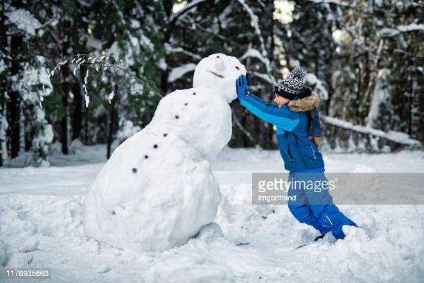 little boy building a snowman on a winter day - failure stock pictures, royalty-free photos & images