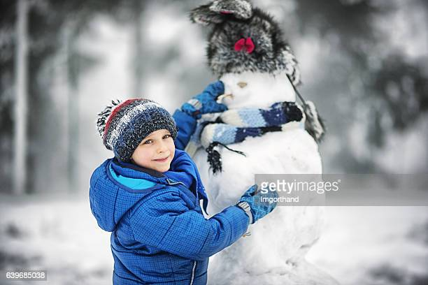 Little boy building funny snowman on a winter day