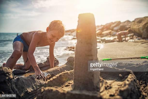 Kleiner Junge Sandburg am Strand von italienischen bauen